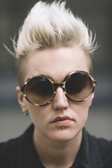 blond butch with mohawk and round sunglasses