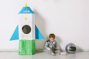 Child wearing handmade astronaut uniform using smart phone next to a diy rocket