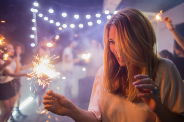 Woman holding sparklers at the party