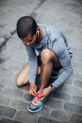 Young black runner ties his shoe befor a run in the street