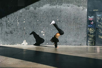 Young african american woman performing break dance in a city
