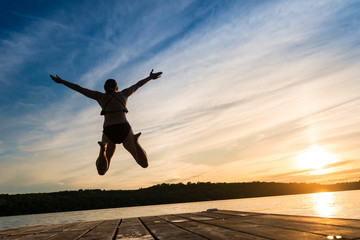 Fun Woman Jumping Into Warm Summer Cottage Lake At Sunset from Dock
