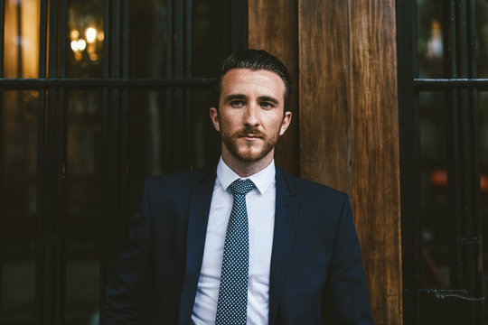 Young businessman wearing a suit standing in front of a wooden door