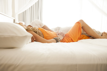 Couple relaxing in bed at luxury resort