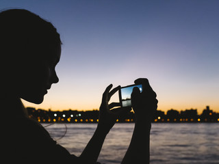 Woman taking pictures with the phone at sunset
