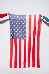 Hands of a couple holding an American flag on white background