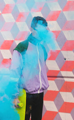 Anonymous person covered with smoke in hip outfit in front of colorful cube pattern wall
