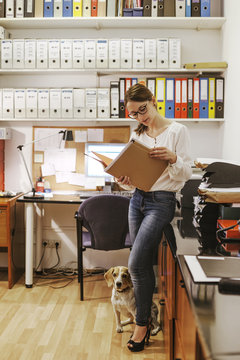 Businesswoman working at office with her dog