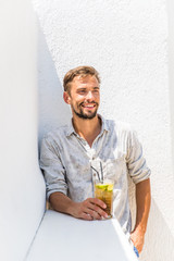 Bearded man drinking cocktail in a white bar