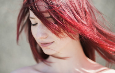 young woman with red hairs and wind
