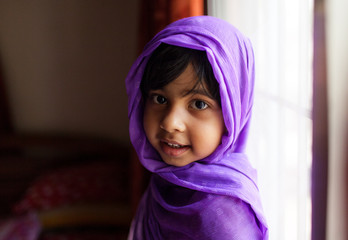 Portrait of cute little girl with her head wrapped in a purple scarf