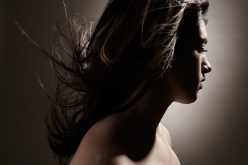 Silhouette of woman with hair blowing in the studio