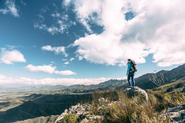 Female hiker with backpack on a mountain summit enjoying the view