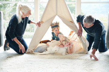Family playing in teepee tent in living room together