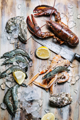 Seafood Lobster, langoustine, oysters and king prawns on ice with lemon on wooden background