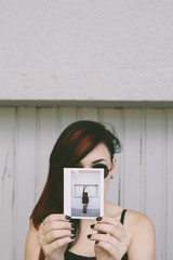 A punk woman holding instant photo