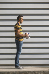 Black man standing with soccer ball on cityscape