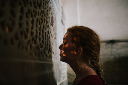 A young woman gazes through a carved stone screen in a historical building