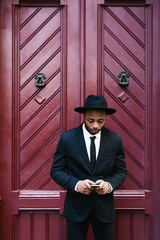 Businessman standing in front of a door using phone
