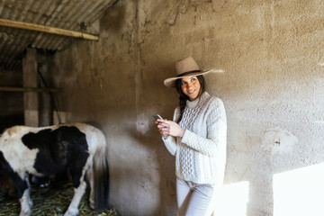 Portrait of a woman farmer using her phone on animal stable