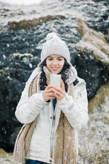 Smiling female with smartphone on Icelandic background