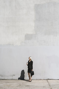 Cool businesswoman against a big wall