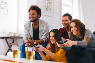 Group of happy young friends playing video games at home
