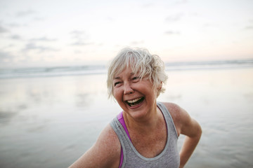 Vibrant mature woman enjoying herself on the beach at sunset