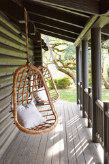 Swing chairs on porch of modern design log cabin
