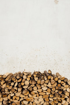 Pile of firewood against the white wall