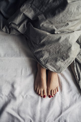 Woman's Feet Under a Duvet