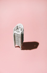 White chairs stacked on pink background