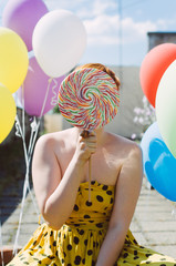Young female holding a big lollipop in front of her face