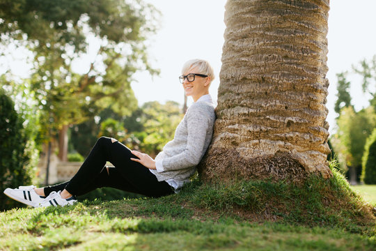 Blonde woman wearing rimmed glasses sitting on the park