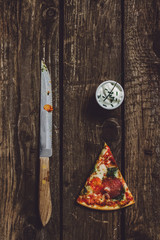 slice of a pepperoni pizza, knife and sour cream dip on wooden background