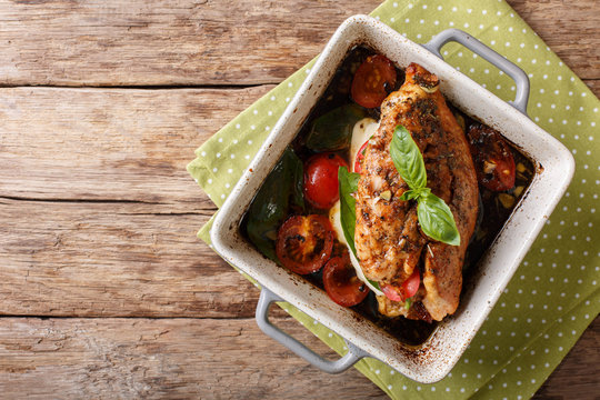 Balsamic chicken stuffed with caprese close-up in a baking dish. Horizontal top view