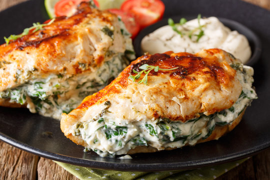 Fried chicken breasts filled with cheese and spinach, and with sauce close-up. horizontal