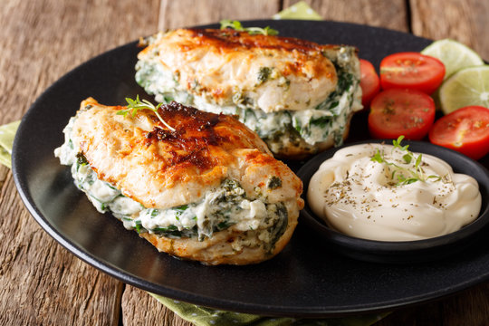 Baked Chicken fillet stuffed with cheese and spinach with sauce close-up. horizontal