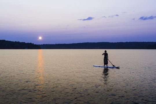Woman Wearing Dress On Stand Up Paddleboard At Cottage Lake
