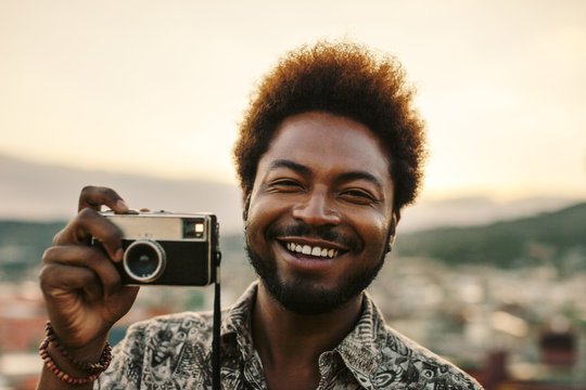 Young black man holding an old camera at sunset
