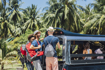 Tourists Enjoying a Taxi Ride in a Tropical Country