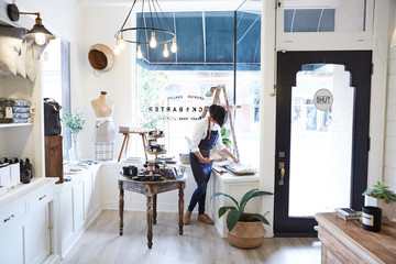 Millennial small business owner stocking shelves in artisan retail shop