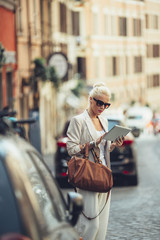 Blonde Caucasian Woman Using a Tablet on the Street