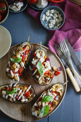 Roasted aubergine stuffed with spiced vegetables and cheese on a table