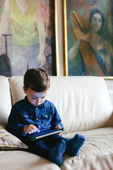 Kid using his digital tablet at home