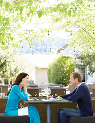 Beautiful couple eating at outdoor restaurant at luxury resort