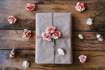 Gift wrapped in brown paper and decorated with flowers made from paper