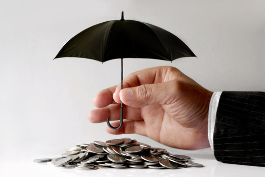 Businessman Protecting Coins With Umbrella. Financial safety Concept.