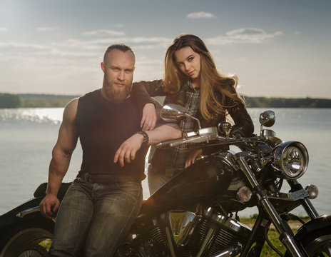 Two people and bike - young woman and bearded man near motorbike. Adventure and vacations concept.