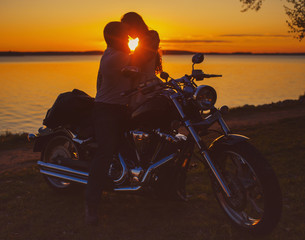Two lovers with motorbike at sunset on the shore of the lake